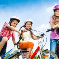 Three laughing kids in helmets hold bike handle-bars and are ready to ride a bike