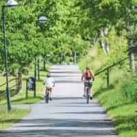A parent bikes alongside their child