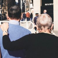 Senior holding the shoulder of man to support each other