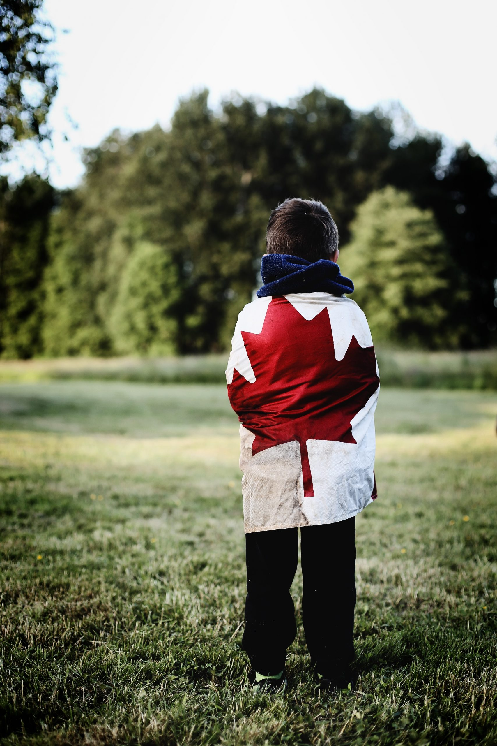 Youth wrapped in Canadian flag on the field
